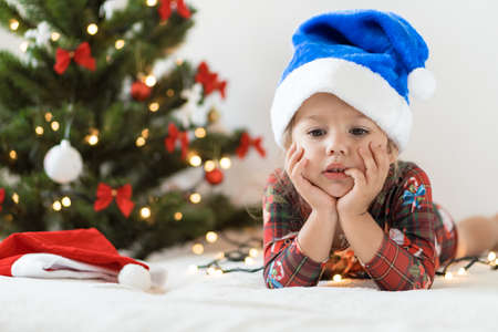 merry xmas and happy new year, childhood, holidays concept - close-up little sad girl in blue santa claus hat on his tummy play and have fun on bed with decorationsand lights on christmas tree. Standard-Bild