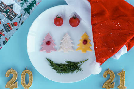 Xmas, winter, new year concept - Christmas them layout on white plate depicts food smiling face with 2021 gold candles and santa hat on blue background