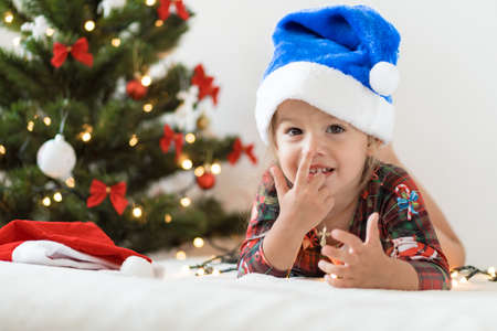 merry xmas and happy new year, childhood, holidays concept - close-up little funny girl in blue santa claus hat on his tummy play and have fun on bed with decorationsand lights on christmas tree.