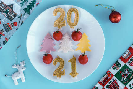 Xmas, winter, new year concept - white plate on which there are three Christmas trees cut from sausage cheese bread with cherry tomatoes and golden candles in form of numbers 2021 on Blue background