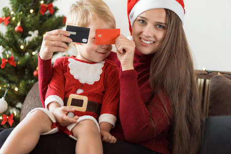 Xmas, winter, new year, Celebration, family concept - joyful mom doing shopping online with small funny kid boy with santa hat and showing discount cards sit near Christmas tree, gifts for relatives