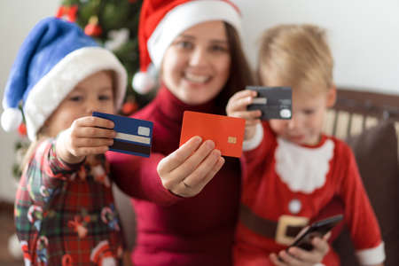 Xmas, winter, new year, Celebration, family concept - joyful mom doing shopping online with two small funny kids with santa hat and showing discount cards sit near Christmas tree, gifts for relatives
