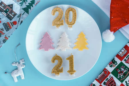 Xmas, winter, new year concept - layout white plate on which there are three Christmas trees cut from sausage cheese bread with santa hat and golden candles in form of numbers 2021 Blue background