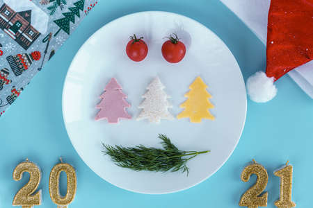 Xmas, winter, new year concept - Blue Christmas background with red gold and white tree toys, Santa hat, 2021 number candles and toy bicycle with gift in trunk. Flatly, top view, overhead. Copy space