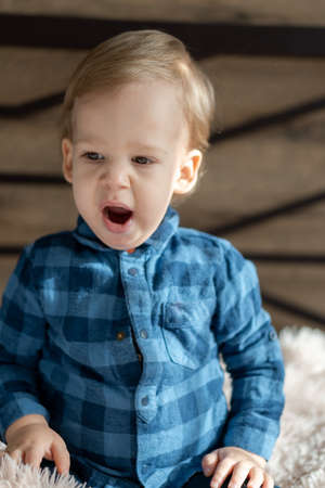 childhood, infant, minor concepts - one blonde black-eyed sad, yawns child as if singing baby boy on soft powdery bed in sunny room. portrait embarrassed preschool Slavic kid in shirt at home indoors