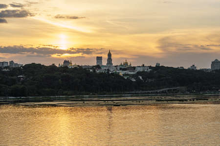 Tourism, sights, historical, Christianity concept - aerial view of banks of Dnieper River in Kiev and ancient monastery buildings Kiev-Pechesk Lavra with beautiful clouds at sunset on summer evening.