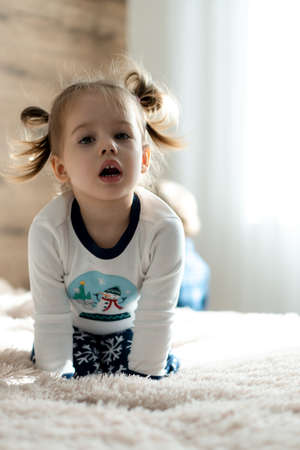 childhood, technology, infant, minor concepts - one cute child baby girl watch cartoon on phone, smartphone on soft white bed in sunny room. kid in pajamas speak by video conference on gadget indoors Standard-Bild