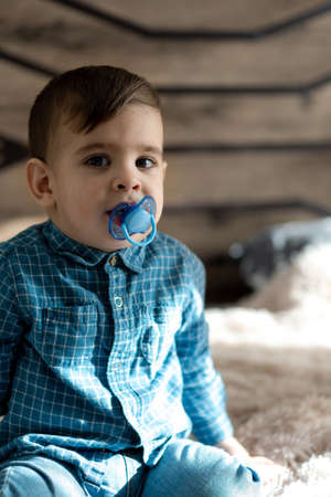 Childhood, family, loneliness concepts - Little preschool black boy in blue clothes Persian Arab appearance of two years of mixed nationality sitting on soft light bed with pacifier in mouth at home