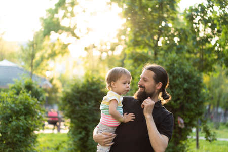 Fatherhood, parenthood, childhood, caring, summer and leisure concept - young dad with beard and long hair in black t-shirt holds in his arms little son in the backlight of the sunset in the park.
