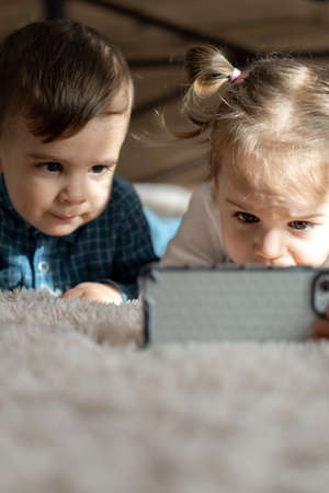 Two young children watch cartoon on smartphone