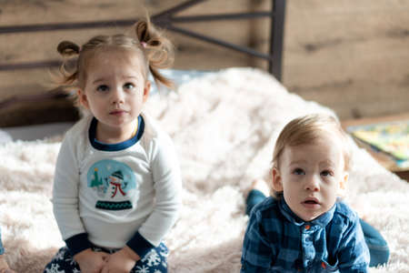 soft focus friendship, childhood, technology concepts - two minors children siblings watch cartoons on phone, smartphone indoor. Infant baby kids brother, sister speak by video conference on gadget