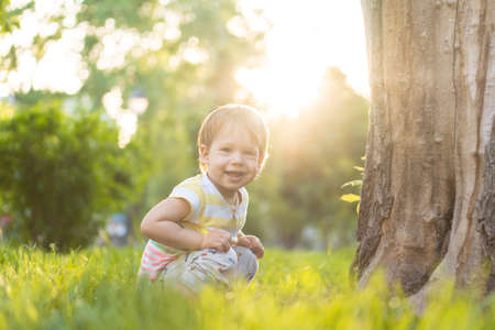 Childhood, nature, summer, parks and outdoors concept - portrait of cute blond-haired little boy in striped multi-colored T-shirt with serous, sad look in backlight of sunset in park. Copy space. Standard-Bild