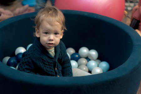 Childhood, infants, development concept - portrait of small preschool minor, fair-haired child boy of 1-2 years old in arena with small colored balls. Kid without emotions sad or scared in playroom Standard-Bild