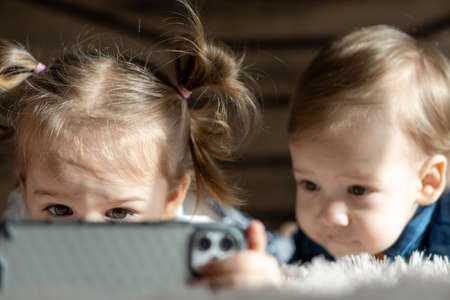 soft focus friendship, childhood, technology concepts - two minors children siblings watch cartoons on smartphone indoor. Infant baby kids brother, sister preschool speak by video conference on gadget