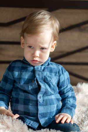 childhood, infant, minor concepts - close up one blonde black-eyed sad, offended child baby boy on soft powdery bed in sunny room. portrait embarrassed preschool Slavic kid in shirt at home indoors