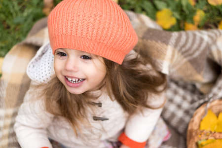 Childhood, family, infant, motherhood, autumn concept - top view Little smiling joyful cute preschool minor blonde girl in orange beret sits on plaid with yellow fallen leaves in cold weather in park