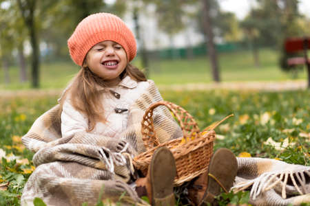 Childhood, family, infant, motherhood, autumn concept - Little cute preschool minor blonde girl in orange beret sits on plaid with basket and yellow fallen maple leaves laughs smiling with closed eyes
