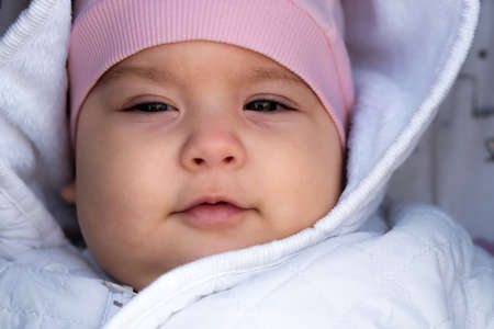 infant, childhood, emotion concept - close-up of cute smiling portrait face of brown-eyed chubby newborn awake toothless baby 6-9 month old looking at camera lying in white jacket pink hat in stroller