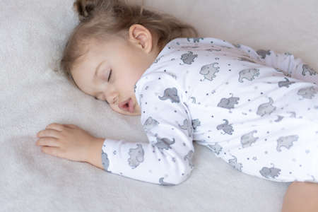 Childhood, care, motherhood, health, medicine, pediatrics concepts - Close up Little peace calm todler preschool girl sleeps resting take deep nap laying on tummy on soft bed. bedtime mod close eyes