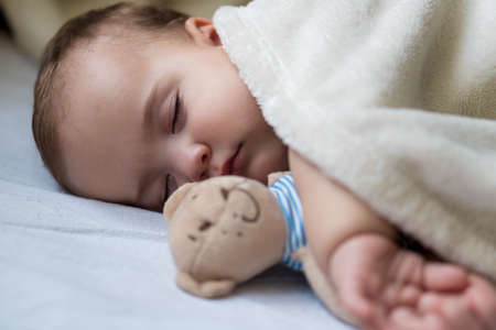 Childhood, care, motherhood, health concepts - Close up Little peace calm infant toddler baby girl sleep resting take deep nap laying hug teddy bear toy on soft warm blanket with close eyes on big bed