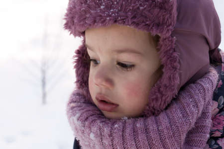 Winter, family, childhood concepts - close-up portrait authentic little preschool minor girl in pink look around in snowy frosty weather. surprised mysterious worried kid face outdoors. copy space