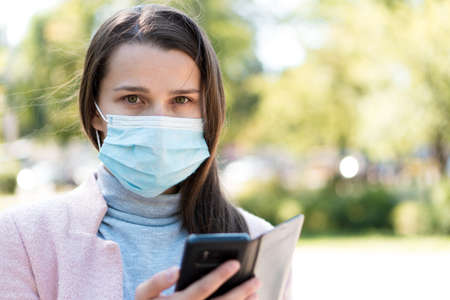Young cute long haired woman European Caucasian Slavic appearance in medical protective mask uses smartphone in midday sunlight backlight in park Stockfoto