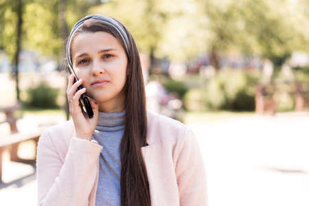 Young happy nice cute long haired smiling woman European Caucasian Slavic appearance in pink and grey talking on phone in midday sunlight backlight in park Stockfoto