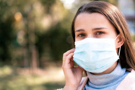 care, infants, spring, coronavirus and quarantine concept - Young cute long haired woman European Caucasian Slavic appearance put on blue medical protective mask in midday sunlight backlight in park.