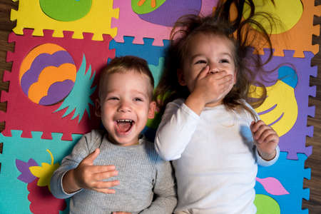childhood, family friendship, games - close up portrait Two funny joy happy smiling little toddler peschool kids siblings twins brother with sister have fun lie laughing on puzzles mat at home indoors Stockfoto