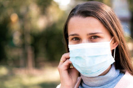 care, infants, spring,  quarantine concept - Young cute long haired woman European Caucasian Slavic appearance put on blue medical protective mask in midday sunlight backlight in park. Stockfoto