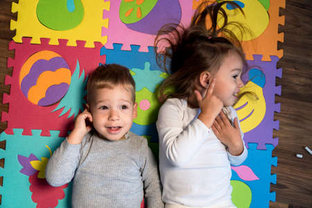childhood, family friendship, games - close up portrait Two funny joy happy smiling little toddler peschool kids siblings twins brother with sister have fun lie playing on puzzles mat at home indoors Stockfoto