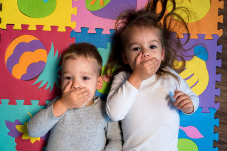 childhood, family friendship, games - close up portrait Two funny happy little toddler peschool kids siblings twins brother with sister have fun cover mouth with hands playing on mat at home indoors