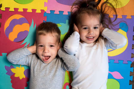 childhood, family friendship, games - close up portrait Two funny joy happy smiling little toddler peschool kids siblings twins brother with sister have fun cover ears playing on mat at home indoors