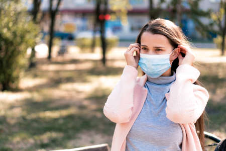 care, infants, spring and quarantine concept - Young cute long haired woman European Caucasian Slavic appearance put on blue medical protective mask in midday sunlight backlight in park.