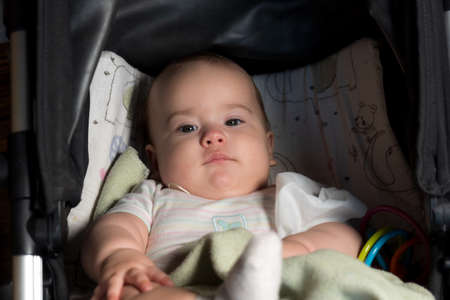 infant, childhood, emotion concept - pretty cute smiling sad sleepy face of big brown-eyed chubby newborn awake 7 months baby girl in white looks at camera lying in black stroller covered by blanket