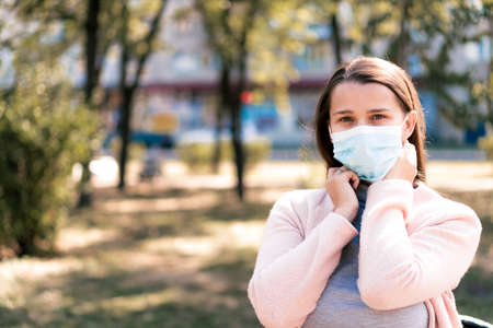 care, infants, spring,    quarantine concept - Young cute long haired woman European Caucasian Slavic appearance put on blue medical protective mask in midday sunlight backlight in park.