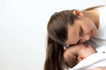 close-up portrait of mom with newborn baby on white background copy space. Young cute caucasian woman black haired holding child in arms motherhood, infancy, childhood, family, Mothers day concept