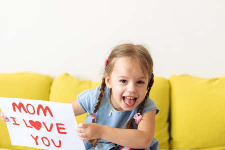 smiling little preschool child girl holding greeting card for Happy Mothers Day with drawn red heart. Loving caucasian baby wishes mom happy birthday confesses his love. Motherhood, childhood concept