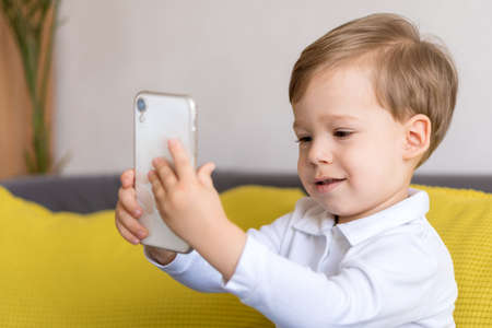 close-up happy little cute preschool baby boy talking video conference by smartphone in living room at home on yellow gray sofa with happiness smile. Childhood, online communication, tehnology concept
