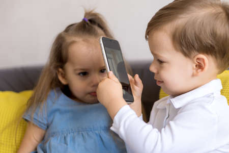 happy and sad little cute preschool siblings baby brother and child sister talk video conference on yellow gray sofa. boy photographs sad displeased girl with smartphone. Childhood, tehnology concept
