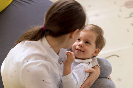 caucasian family little preschool baby boy and mom young woman hug joyfully together in living room at home with happiness smile. Child son congratulates on Mothers Day. Motherhood, childhood concept