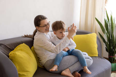 caucasian family little preschool baby boy and mom talking video conference by smartphone together in living room at home with happiness smile. activity technology lifestyle mobile phone use concept