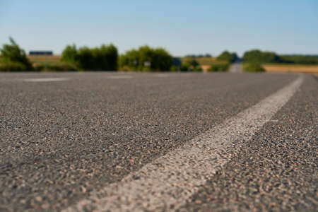 soft focus asphalt road surface with white markings close-up from the low shot. blured country road and field with forest in summer. High quality photo. Travel, tehnology, nature comcept. Фото со стока
