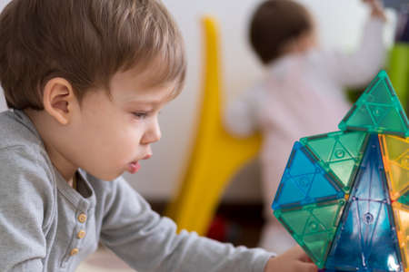 close-up little cute preschool child boy 2-3 years builds building from colored magnetic construction. Baby plays in kids room. child creates tower of geometric shapes. Childhood, tehnology concept Фото со стока