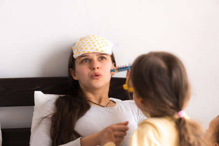 Cute little girl wearing uniform playing doctor or nurse with young mum or nanny in bedroom, makes an injection, measures temperature, family spending leisure time at home together, role play game