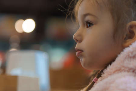 authentic portrait little handsome blond sad girl sitting in cafe in evening alone. Preschool toddler kid child eating and drinking fast food lunch in restaurant. Family, childhood, health, rest