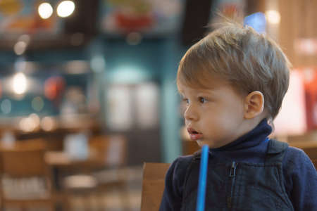 authentic portrait little handsome blond sad boy sitting in cafe in evening alone. Preschool toddler kid child eating and drinking fast food lunch in restaurant. Family, childhood, health, rest