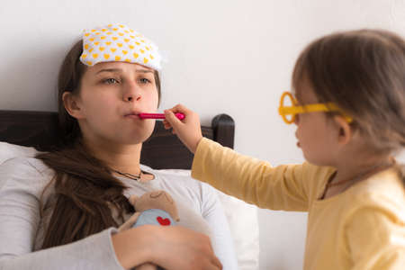 Cute little girl wearing uniform playing doctor or nurse with young mum or nanny in bedroom, checking mother throat, measures temperature, family spending leisure time at home together, role play game