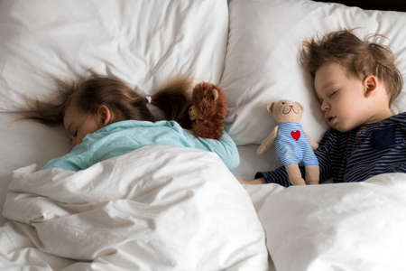 Authentic portrait cute caucasian little preschool siblings baby boy and girl in blue sleep with teddy bear on white bed. child resting at lunchtime. care, medicine and health, Childhood, life concept