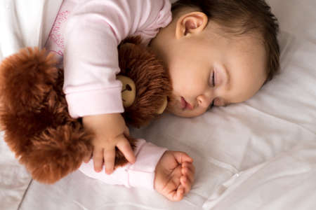 Authentic portrait cute caucasian little infant chubby baby girl or boy in pink sleep with teddy bear on white bed. child resting at lunchtime. care, Sleeping kid, Childhood, Parenthood, life concept